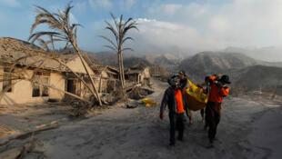 Corpos de vítimas do vulcão Merapi são levados por socorristas no vilarejo de Kinarrejo.