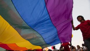 A giant rainbow flag at a demonstration against homophobia.
