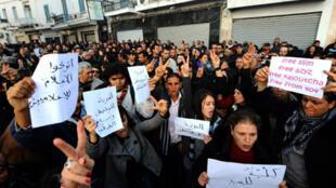Des manifestants brandissent des affiches et font des signes de victoire pendant un rassemblement à Tunis le 8 janvier 2011, soit six jours avant que Zine el-Abidine Ben Ali n'abandonne le pouvoir.