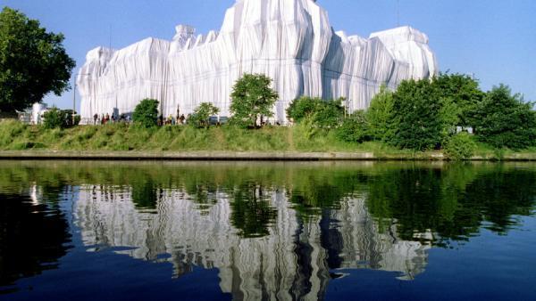 В 1995 году Христо обернул берлинский Рейхстаг в 100 тысяч квадратных метров серебристой ткани.