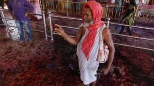 Un sadhu prend une photo avec son téléphone portable durant holi : la fête des couleurs, le 17 mars 2014.