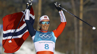 Gold medallist Marit Bjoergen of Norway celebrates victory with her national flag.