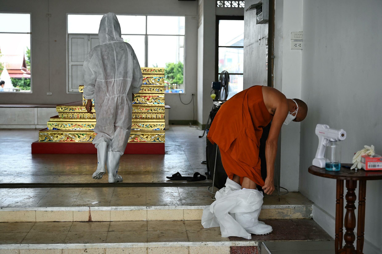 Un monje budista se quita su traje de protección tras haber incinerado a víctimas del covid-19, en Wat Chin Wararam Worawihan, Bangkok, el 30 de julio de 2021