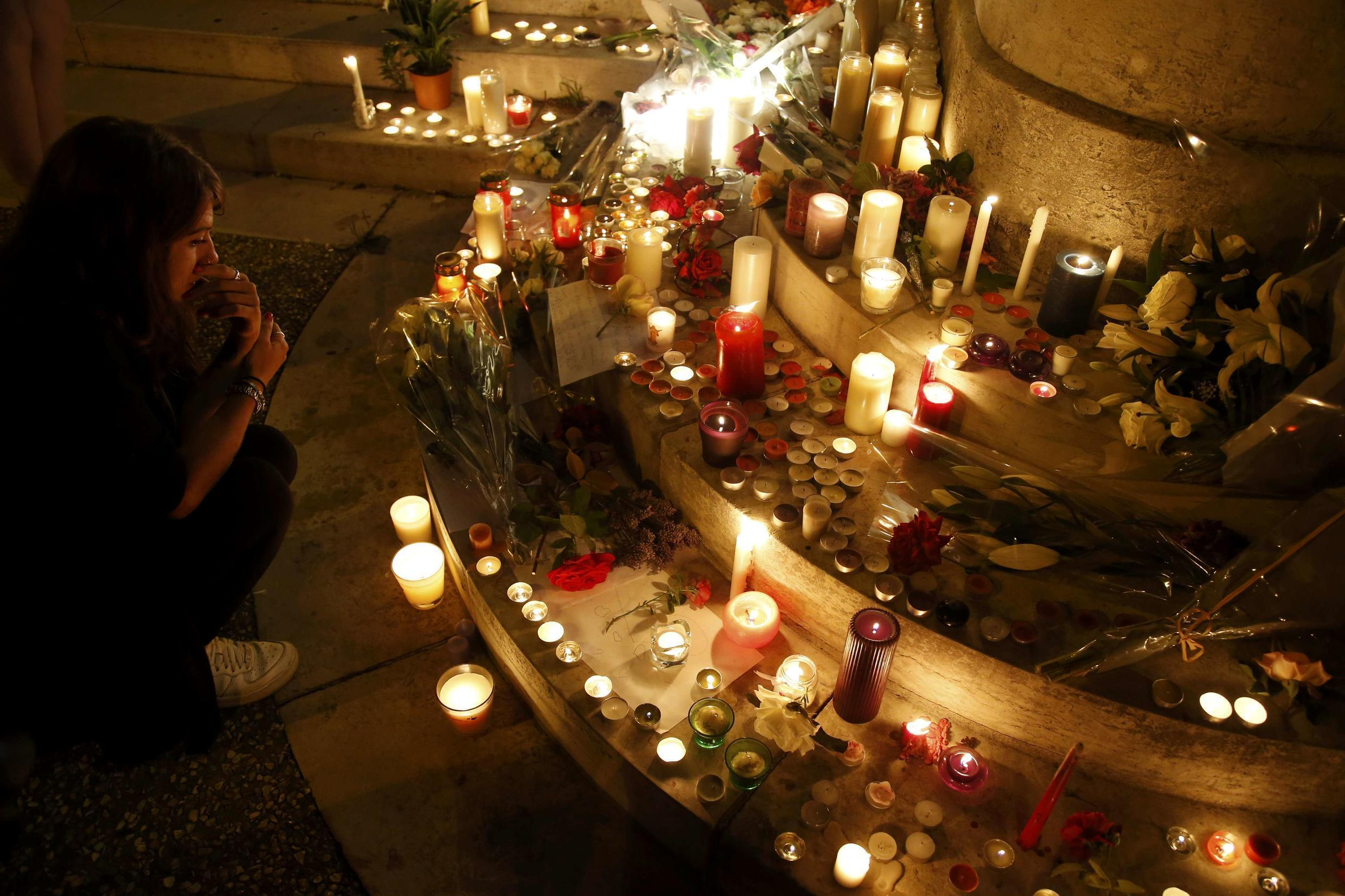 A woman sits near flowers and candles at the town hall in Saint-Etienne-du-Rouvray, near Rouen, to pay tribute to French priest, Father Jacques Hamel who was killed with a knife on Tuesday.