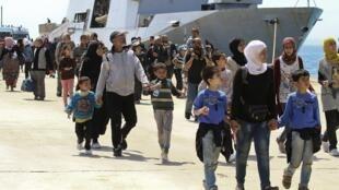 Des migrants débarquent dans le port d'Augusta en Sicile, après avoir été secourus par un navire, le 22 mai 2014.