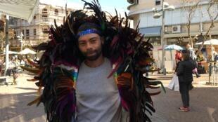 O designer natalense Franklin Tavares Praxedes veste um cocar confeccionado por ele nas ruas de Tel Aviv