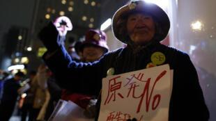 Una mujer levanta el puño y muestra una pancarta con un mensaje antinuclear durante una manifestación. Japón, el 10 de marzo de 2016.