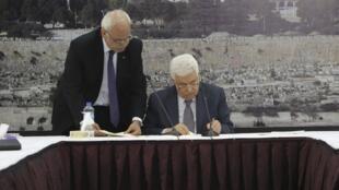 A Ramalllah, le 31 décembre 2014, le président palestinien Mahmoud Abbas signe des conventions internationales, dont celle de l'adhésion à la Cour pénale internationale.