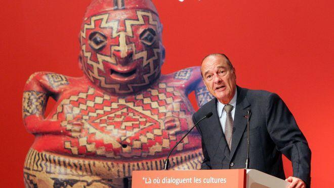 Jacques Chirac durante la inauguración del museo en el 2006, al fondo, la imagen de la pieza adquirida en 1998 y emblema de este museo.