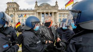 5月16日,示威者在德國柏林的國會大廈前,抗議政府禁令,戴着防護口罩的警察拘留了示威者。