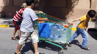 Libia: niños transportando botellones de agua en un carrito por las calles de Trípoli, 1° de septiembre de 2011.