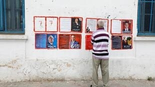 A man looks election posters of presidential candidates in Tunis, Tunisia September 2, 2019.
