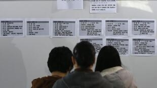 一个韩国家庭正在读失事死亡失踪者名单  2014.4 21