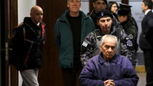 Les prêtres Nicola Corradi (R) et Horacio Corbacho, ainsi que l'ancien jardinier Armando Gomez, sont escortés hors de la salle d'audience à Mendoza,  le 5 août 2019.