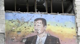 Painel bombardeado em Damasco traz imagem do presidente sírio Bashar al-Assad.