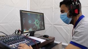 Un employé du ministère de la Santé irakien délivrant des conseils sur les mesures de précaution contre le coronavirus dans une station de radio à Basra, le 13 juillet 2020.