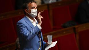 El diputado centrista François-Michel Lambert exhibe un porro y un vaso con una hoja de cannabis dibujada en la Asamblea Nacional francesa, en París, el 4 de mayo de 2021