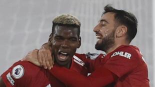 Le milieu de terrain français de Manchester United, Paul Pogba, auteur du 2e but pour son club, est félicité par son coéquipier portugais, Bruno Fernandes, lors du match de Premier League contre Fulham, le 20 janvier 2021 à Londres