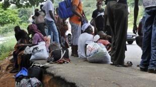 Des habitants de Yopougon attendent des véhicules pour quitter leur quartier, le 20 avril 2011.