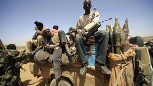 Rebel forces sit on a vehicle as they guard during the visit of Joint Special Representative (JSR) Ibrahim Gambari