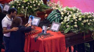 Les gens pleurent à côté des cercueils contenant des corps de victimes de l'effondrement du pont de Gênes, au parc des expositions de Gênes, en Italie, le 18 août 2018.