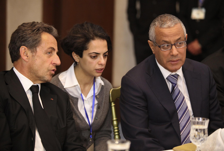 Libya's Prime Minister Ali Zeidan (R) sits with former French President Nicolas Sarkozy (L) and a translator in Tripoli