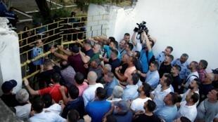 Des partisans de l'opposition manifestent devant un bâtiment scolaire désigné comme bureau de vote, lors d'une manifestation antigouvernementale à Kavaja, le 19 juin 2019.