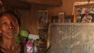 Antoinette Akpadji, un des relais communautaires du village de Houangon, chez elle devant la cantine qui continent le test rapide du paludisme et des médicaments essentiels.