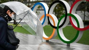 Un passant masqué passe devant les anneaux olympiques près du Musée olympique à Tokyo, le 28 janvier 2021