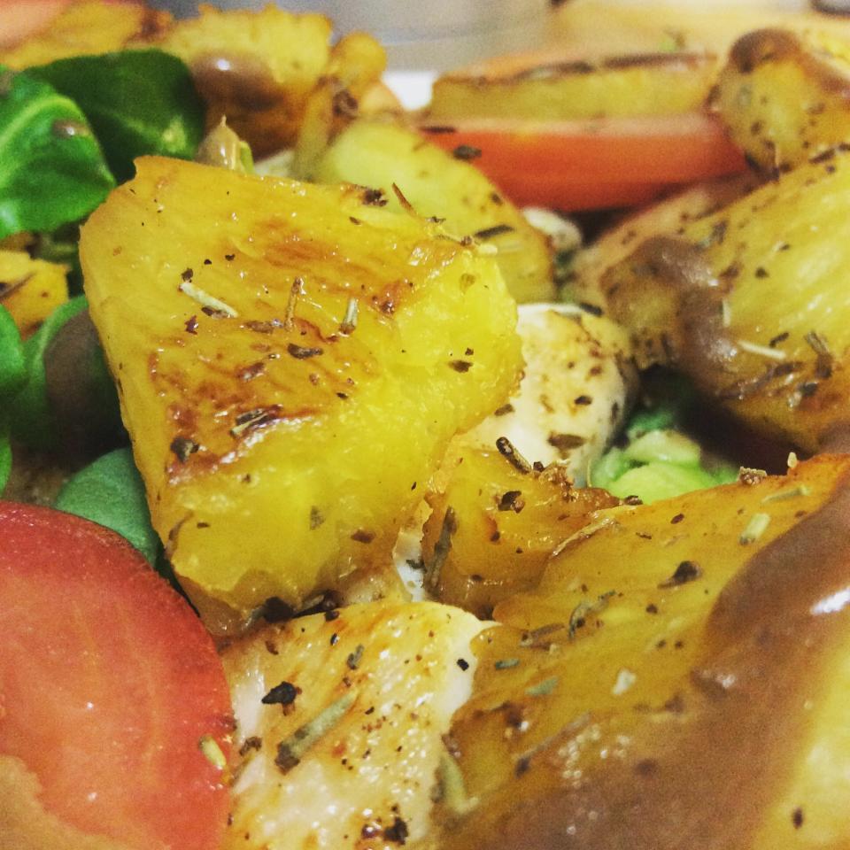 Gros plan d'un morceau d'ananas rôti accompagnant une salade.