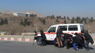 Des journalistes afghans s'abritent derrière une ambulance près de l'hôtel Intercontinental lors d'une attaque par des hommes armés à Kaboul le 21 janvier 2018.