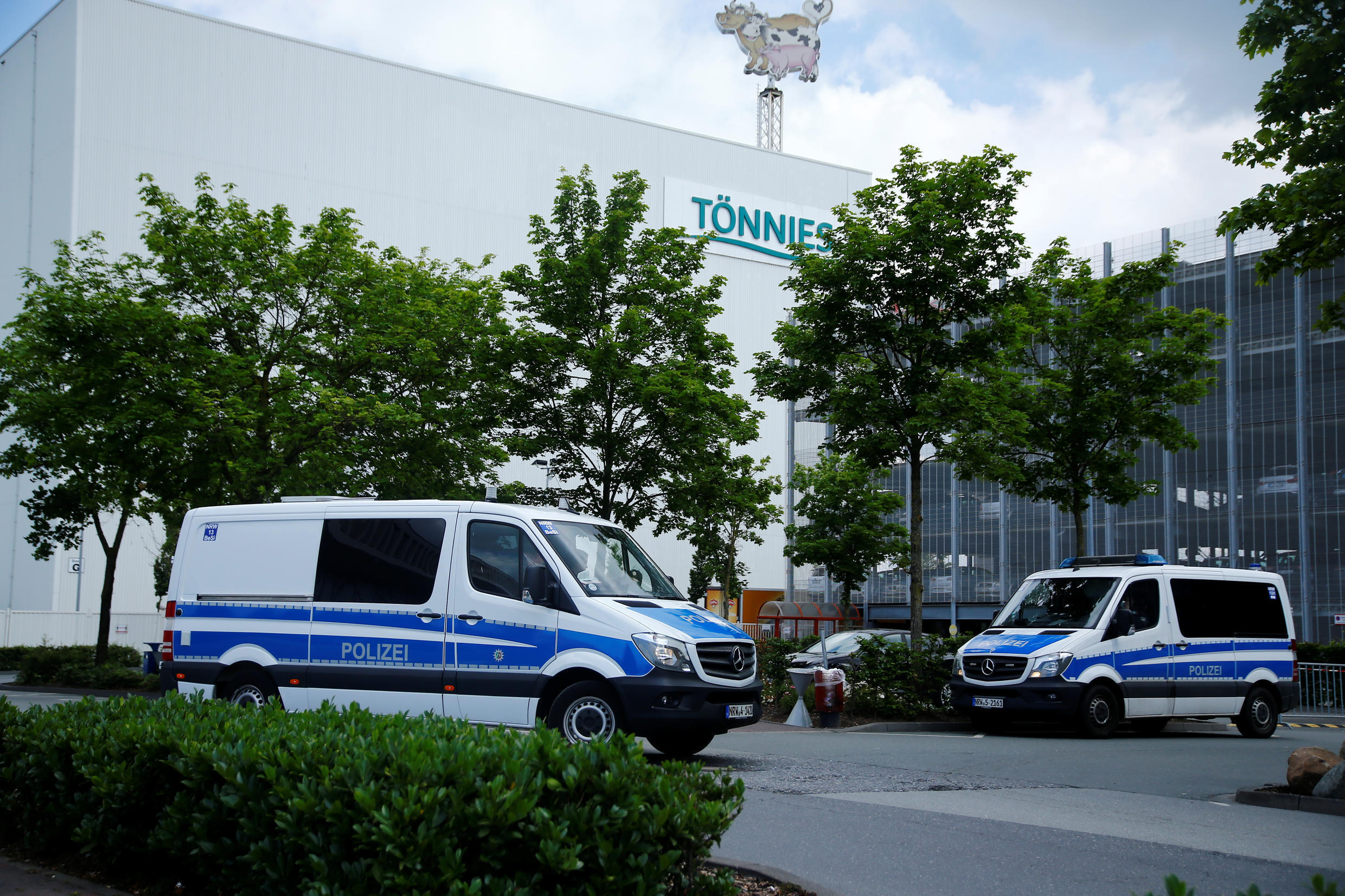 Police vehicles are seen outside the main Toennies meat factory that had to be shut down because of the coronavirus disease (COVID-19) outbreak among its employees, in Rheda-Wiedenbrueck, Germany June 20, 2020.