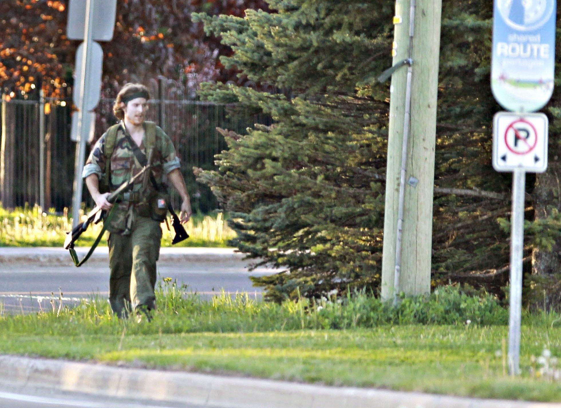 Imafgem de Justin Bourque caminhando pelas ruas de Moncton fortemente armado em 4 de junho de 2014.