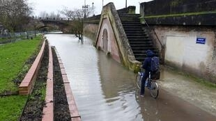 A cyclist stands on his bike on a Garonne river's flooded bank in Bordeaux, southwestern France, on 13 December 2019, following strong winds and heavy rains.