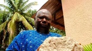 Adama Camara tient dans ses mains un morceau de béton, vestige du pont du 8-Novembre.