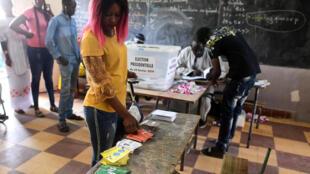 Une femme prend des bulletins avant de voter pour l'élection présidentielle sénégalaise à Dakar, le 24 février.