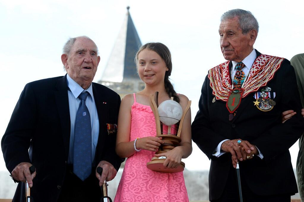 Swedish climate activist Greta Thunberg, flanked by WWII veteran and native American Charles Norman Shay (R), sponsor of the Freedom Award, and French WWII veteran Leon Gautier, poses with the Normandy 'Freedom prize' during award ceremony on July 21
