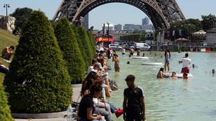 Para enfrentar o calor, teve gente que transformou o chafariz diante da Torre Eiffel em piscina.