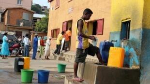 Un homme remplit ses jerricans d'eau à Antananrivo. Les coupures d'eau potabe sont devenues régulières ces derniers temps.