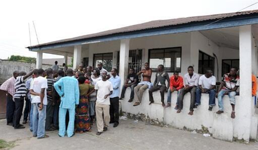 Inhabitants of Ayakoromo gather after a violent battle on 5 December 2010