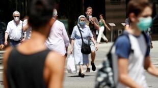 Des espagnols, portant pour la plupart un masque de protection contre le Covid-19, dans la rue à Barcelone, le 8 juillet 2020.