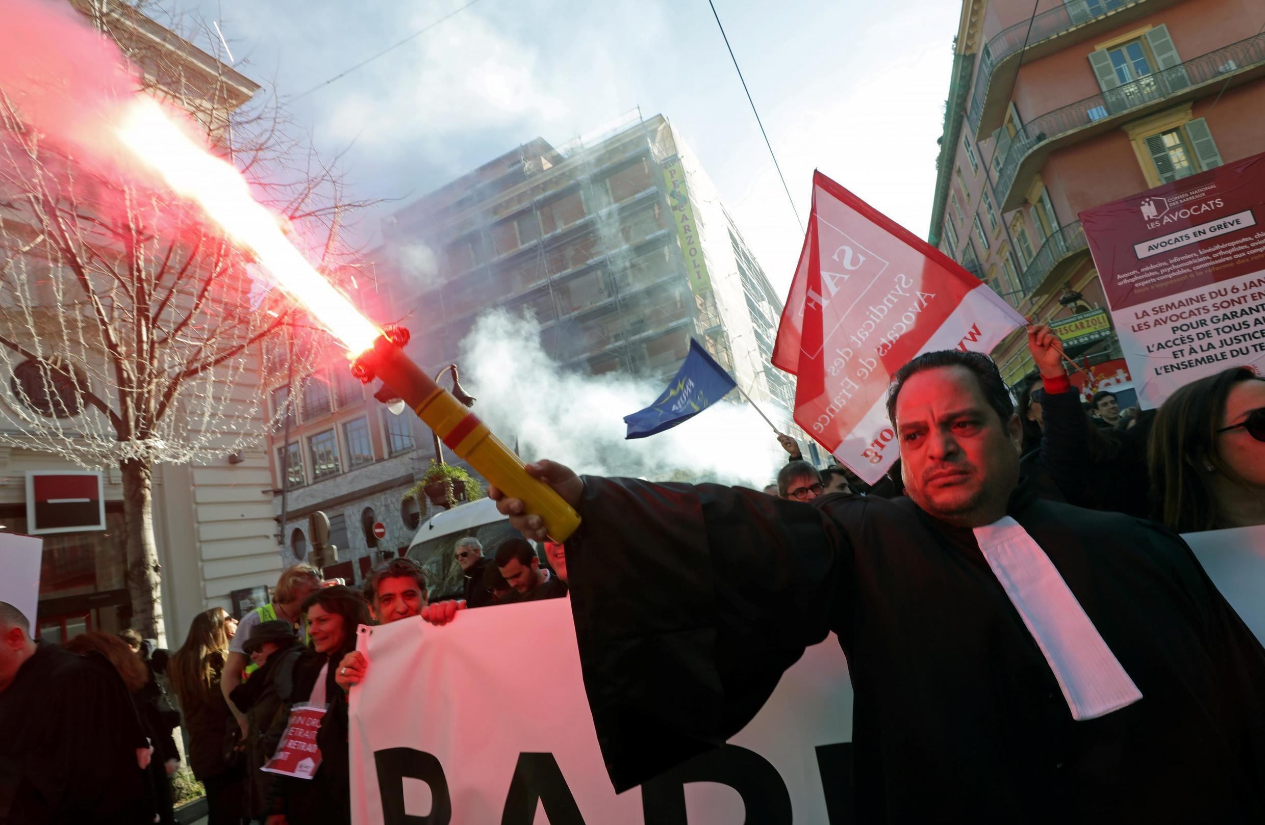 A French lawyer holds a flare as he demonstrates during a strike against French government's pensions reform plans, in Nice, France.
