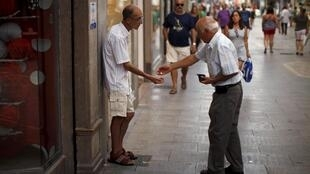 A man gives coins to a beggar as for many ordinary citizens times are harder than ever, La Bola, southern Spain, 27 August 2015.