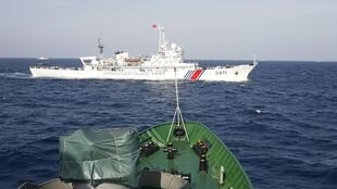 Tàu tuần dương Trung Quốc (màu trắng) cản mũi tàu cảnh sát biển Việt Nam trong vùng biển của Việt Nam (ảnh chụp ngày 14/05/2014)