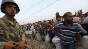 Chegada de refugiados curdos na  fronteira turca perto da cidade de Suruc, no dia 27 de setembro.