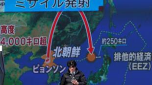 Un hombre frente a una representación del misil lanzado por Corea del Norte. En una calle de Tokyo,  29 de noviembre de 2017.