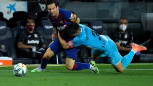 """Lionel Messi, le prodige argentin du Barça, """"plaqué"""" par le défenseur de Leganes Unai Bustinza, lors du match de football opposant les deux équipes au Camp Nou à Barcelone le 16 Juin 2020."""