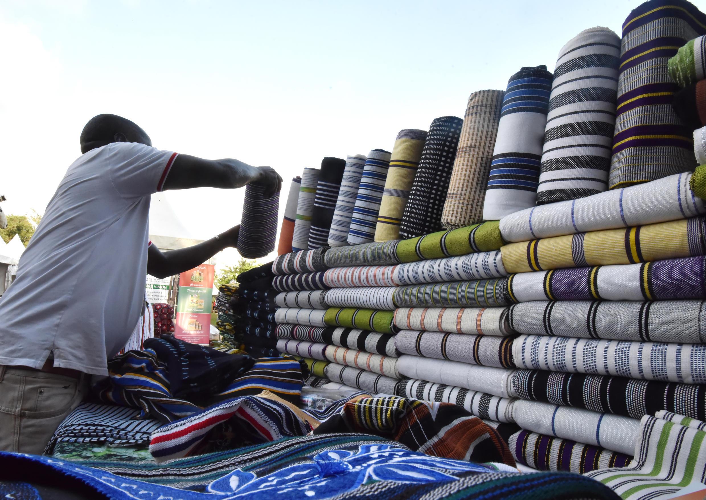 Un exposant burkinabé organise des pagnes Faso-Danfani du Burkina Faso le 12 novembre 2017 à Abidjan lors du salon de la promotion économique et commerciale du Burkina Faso, organisé en Côte d'Ivoire.