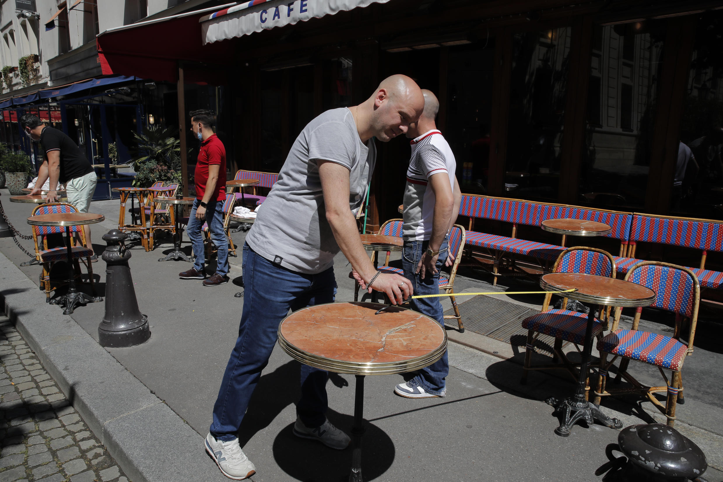 Waiters prepare the terrace of a restaurant in order to respect distancing measures in Paris, as France gradually lifts its Covid-19 lockdown.