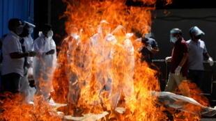 Familiares con equipo de protección personal (EPP) asisten al funeral de un hombre, que murió por la enfermedad del coronavirus (COVID-19), en un crematorio en Nueva Delhi, India el 21 de abril de 2021. REUTERS/Adnan Abidi